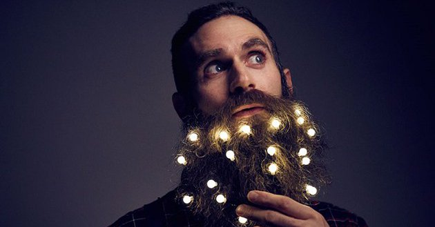 Photo of a man whose beard is festooned with holiday lights. Via themindcircle.com