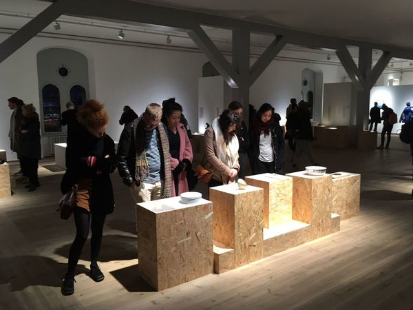"""A photograph taken at the Museum of Broken Relationships: visitors looking at a display of """"brokenship"""" artifacts."""