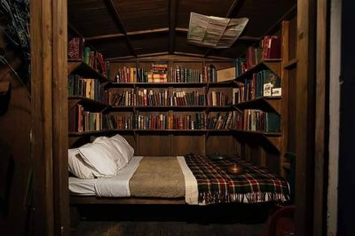 Photo: a charming, rustic sleeping nook, whose walls are lined with books