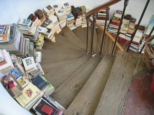Photo: a winding staircase, the wall of which is lined with books