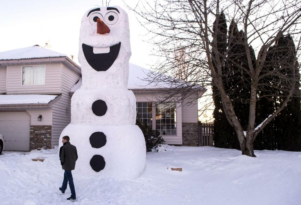 """Photo: """"Clayton Conrad walks past the 22-foot-tall Olaf snowman Wednesday in his front yard . . . in Spokane Valley."""" Via the Spokesman-Review"""